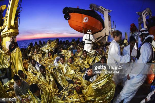 TOPSHOT Migrants and refugees wrapped in survival foil blankets rest next to rescue members aboard the Topaz Responder ship run by Maltese NGO Moas...