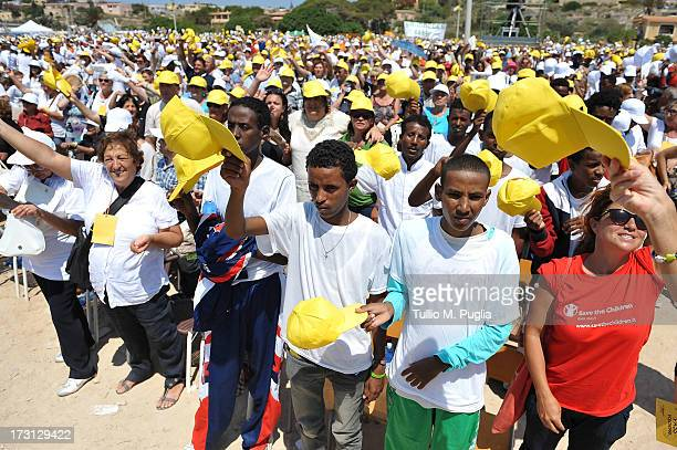 Migrants and residents gather for Holy Mass celebrated by Pope Francis during his visit to the island of Lampedusa on July 8, 2013 in Italy. On his...