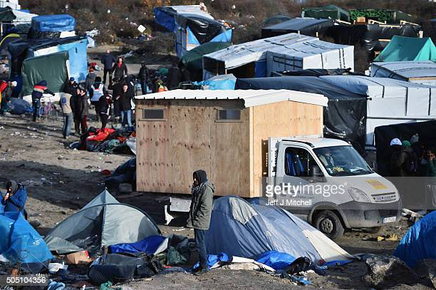 Migrants and volunteers clear part of the camp known as the 'Jungle' on January 15 2015 in Calais France French police have given residents a...