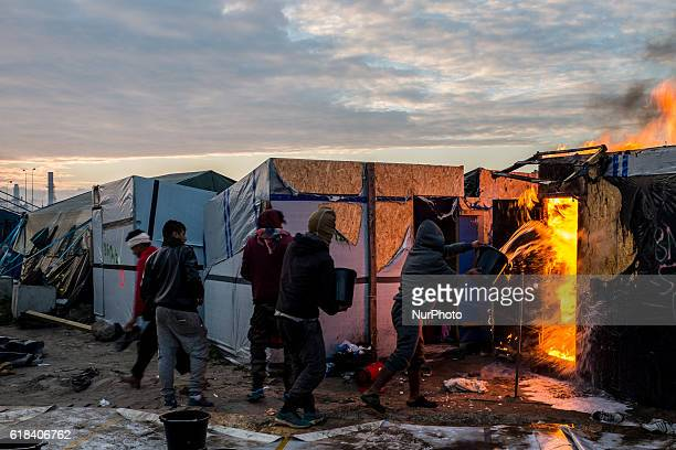 Migrants and Volunteers extinguish in the Calais Jungle a burning hut in Calais France on 26 October 2016 Huge fires destroyed a mayor part of the...