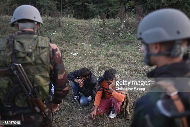Migrants are detained by hungarian soldiers and police after they scaled the fence which is illegal under new laws on September 15 2015 in Roszke...