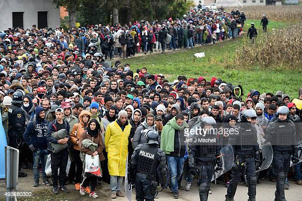 Migrants are escorted by police through Dobova as they walk to a holding camp on October 22 2015 in Dobova Slovenia Thousands of migrants marched...