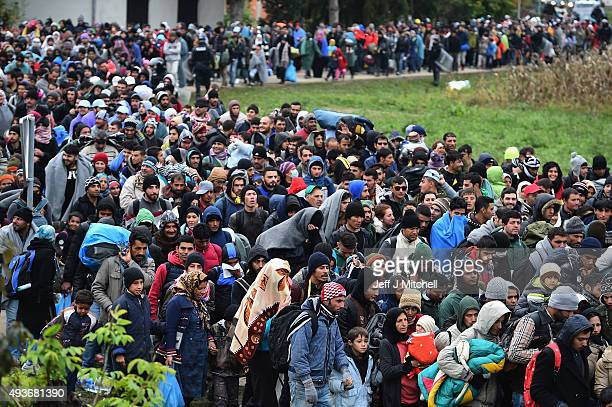 Migrants are escorted by police through Dobova as they walk to a holding camp on October 22, 2015 in Dobova, Slovenia. Thousands of migrants marched...