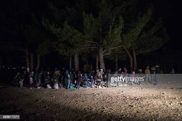 Migrants are illuminated by the headlights of a Greek police car as they wait to cross the border into the Former Yugoslav Republic of Macedonia on...