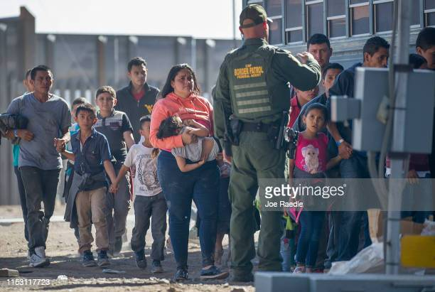 Migrants are loaded onto a bus by US Border Patrol agents after being detained when they crossed into the United States from Mexico on June 01 2019...