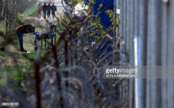Migrants are seen at the 'no man's land' between Hungary and Serbia near the Hungarian border fence at the Tompa border station transit zone on April...