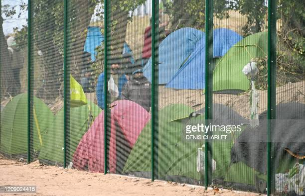 Migrants are seen behind a fence, on April 3, 2020 in Calais, northern France, during an operation to shelter migrants on a voluntary basis in a bid...