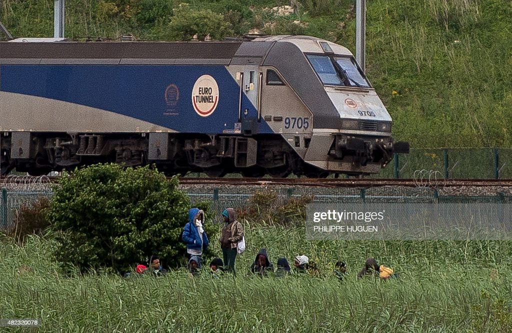 Migrants are seen near a Channel Tunnel train in Coquelles near Calais, northern France, on late July 29, 2015. One man died Wednesday in a desperate attempt to reach England via the Channel Tunnel as overwhelmed authorities fought off hundreds of migrants, prompting France to beef up its police presence.