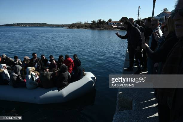 TOPSHOT Migrants are seen on an inflatable boat as local residents prevent them from disembarking in Lesbos island on March 1 2020 Greece said Sunday...