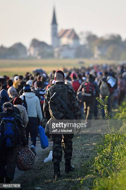 Migrants are taken to a holding camp in the village of Dobova before boarding a train heading towards Austria on October 26, 2015 in Dobava,...