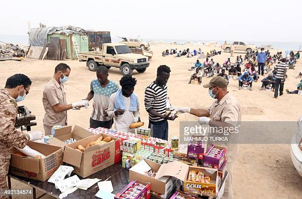 Migrants arrested earlier in the week receive food distribution in Tajura a coastal suburb of the Libyan capital Tripoli on October 10 2015 ahead of...