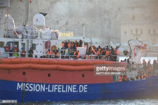 Migrants arrive aboard 'Lifeline' a vessel for the German charity Mission Lifeline in the harbour of Valletta Malta on June 27 2018 A rescue boat...