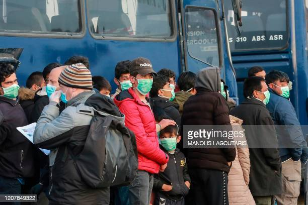 Migrants arrive at the port of Mytilene in the Greek island of Lesbos on March 20 2020 to be transfered in a closed camp in northern Greece as the...