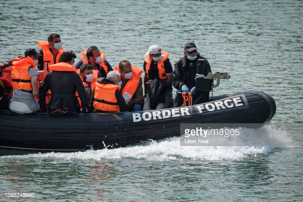 Migrants arrive in port aboard a Border Force vessel after being intercepted while crossing the English Channel from France in small boats on August...