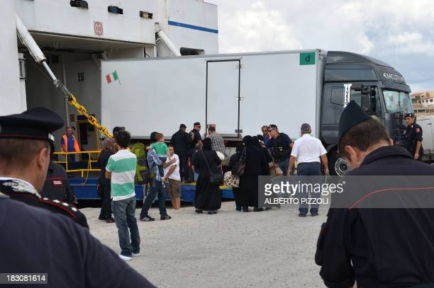 Migrants arrived in Lampedusa few days ago board a ferry to be transferred to Sicily as a truck transporting coffins disembarks on October 4 2013...