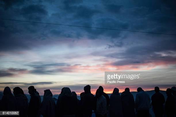 Migrants at sunrise in the camp of Idomeni at the border between Greece and Macedonia At GreekMacedonian border in the camp of Idomeni are massed...