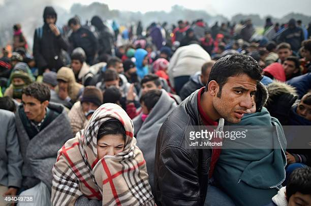 Migrants attempt to keep warm as they are held back by the police near the village of Rigonce, before being walked to Brezice refugee camp on October...