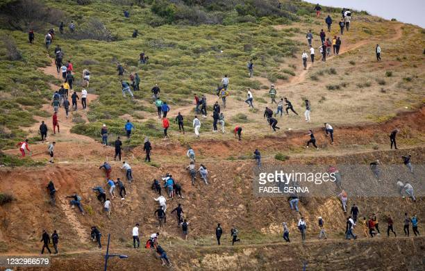 Migrants avoid the Moroccan police as they try to reach the border between Morocco and thr Spanish enclave of Ceuta on May 18, 2021 in Fnideq. - At...