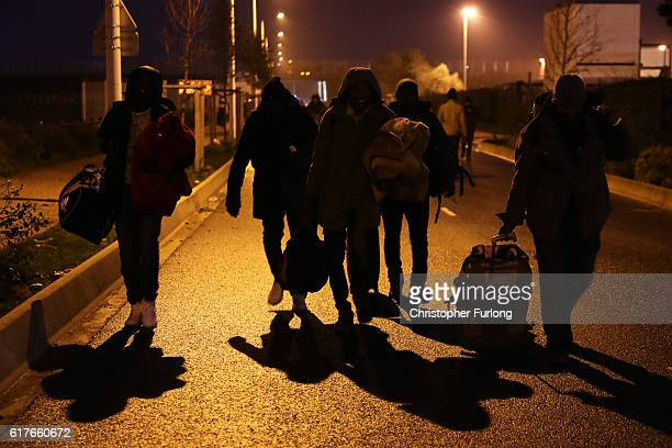 Migrants begin to leave the Jungle migrant camp in the early morning before authorities demolish the site on October 24 2016 in Calais France Police...