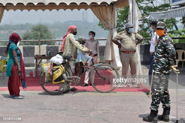 Migrants being stopped by police personnel at Sarai Kale Khan while journeying back to their homes on bicycles during lockdown on May 18 2020 in New...
