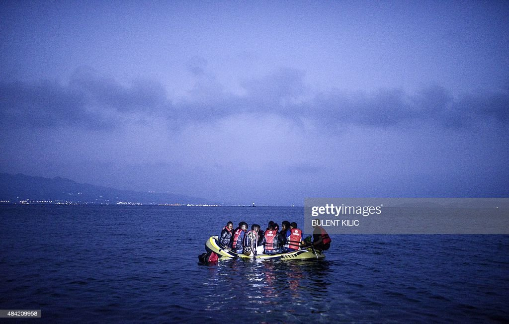 Migrants board a boat to the Greek island of Kos on early August 16, 2015 off the shore of Bodrum, southwest Turkey. Authorities on the island of Kos have been so overwhelmed that the government sent a ferry to serve as a temporary centre to issue travel documents to Syrian refugees -- among some 7,000 migrants stranded on the island of about 30,000 people. The early hours are the safest time for migrants travelling from Turkey to the Greek islands just across the water, which have seen a huge influx of refugees escaping the civil war in Syria and chaos in Afghanistan since the beginning of this year.