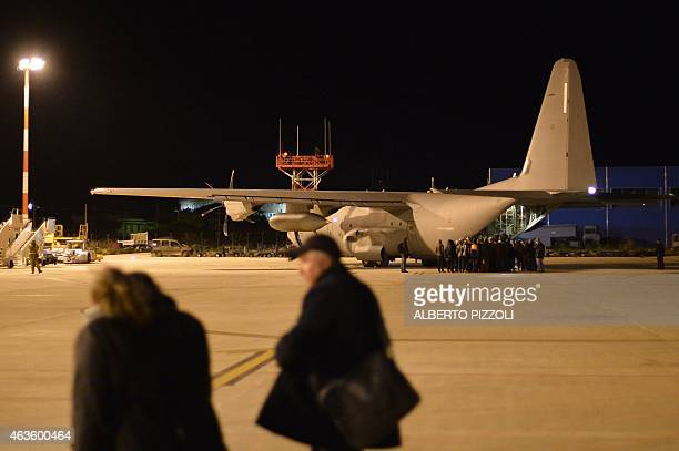 Migrants board a military plane to be transferred on February 16, 2015 at the Lampedusa airport. The Italian coastguard launched a massive operation...