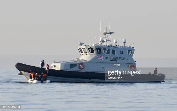 Migrants board an English Border Force vessel after their dingy was passed to English authorities by a French patrol boat on the English Channel, 12...