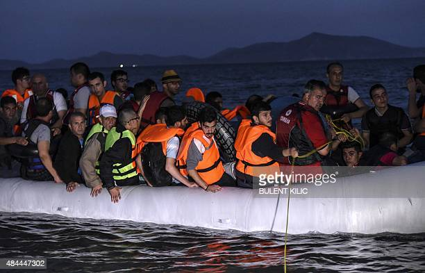 Migrants board an inflatable boat to reach the Greek island of Kos early on August 19 near the shore of Bodrum southwest Turkey The UN refugee agency...