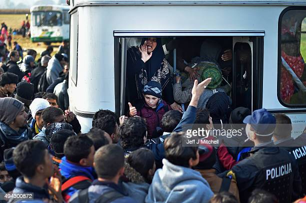 Migrants board buses as they are transported to Brezice refugee camp on October 26 2015 in Rigonce Slovenia Thousands of migrants marched across the...