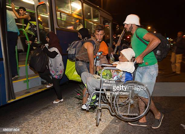 Migrants board buses said to be bound for Austria outside Keleti station in central Budapest on September 4 2015 in Budapest Hungary Earlier today...