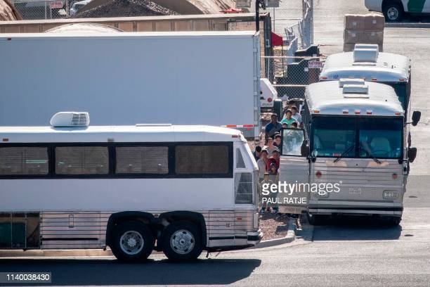 Migrants board buses to take them to shelters after being released from migration detention as construction of a new migrant processing facility is...