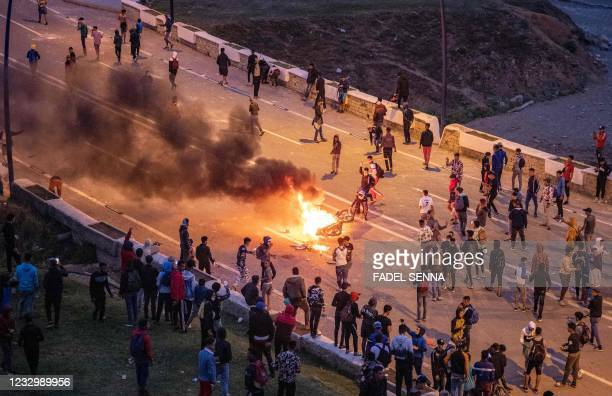 Migrants burn a motorbike as they clash with Moroccan riot police in protest at being stopped from crossing the border, in the northern town of...