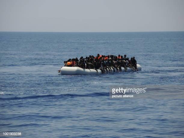 Migrants can be seen aboard a precarious rubber dinghy in the Mediterranean sea 27 July 2017 Photo Lena Klimkeit/dpa