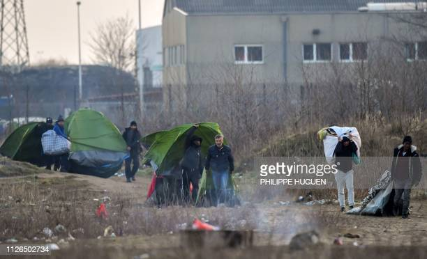Migrants carry back their tents on a camp moments after it was evacuated by police forces on February 21, 2019 in Calais.