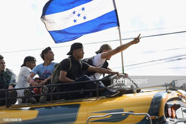 Migrants carry the flag of Honduras while on a caravan of immigrants en route to the Mexican border on October 18 2018 in Guatemala City Guatemala...