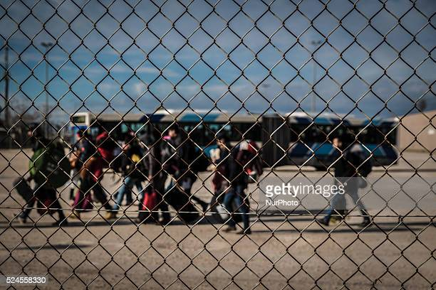 Migrants carry their belongings as they are moved from the former Olympic Tae kwon Do stadium in Faliro in Athens Thursday Dec 17 2015 Migrants are...