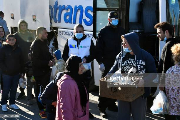 Migrants carry their belongings as they board on buses during the evacuation of a makeshift camp in a park across the City Hall in Sarajevo on May 18...