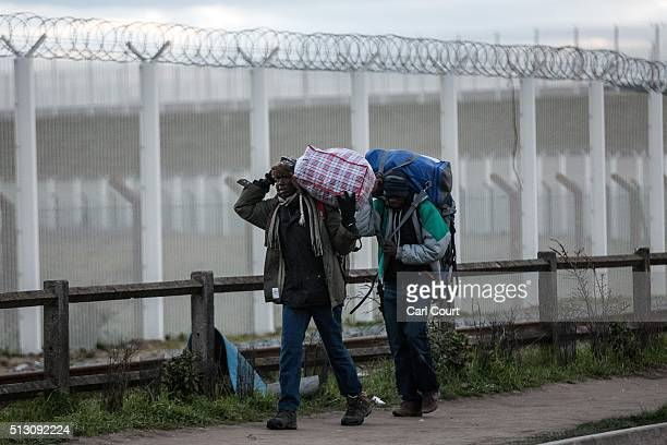 Migrants carry their belongings away from the 'jungle' migrant camp on February 29 2016 in Calais France The French authorities have begun...