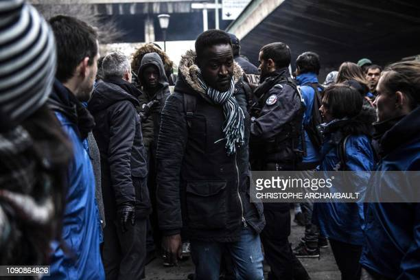 Migrants carry their belongings during the evacuation of a makeshift camp set up under Paris' ring road in the north of Paris' area of Porte de la...