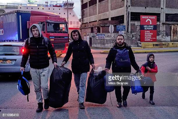 Migrants carry their belongings to a bus station in Pireaus, port of Athens on Februray 18, 2016 in Athens, Greece. Migrants continue to pour into...