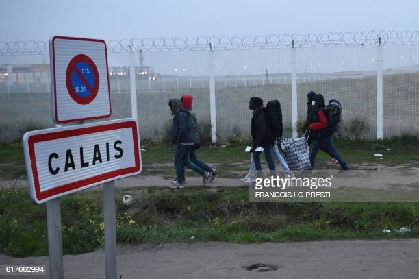 TOPSHOT Migrants carrying their luggage walk past a Calais city limit sign as they head towards an official meeting point set by French authorities...