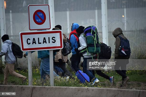 Migrants carrying their luggage walk past the Calais city limit sign as they leave during the full evacuation of the Calais 'Jungle' camp in Calais...