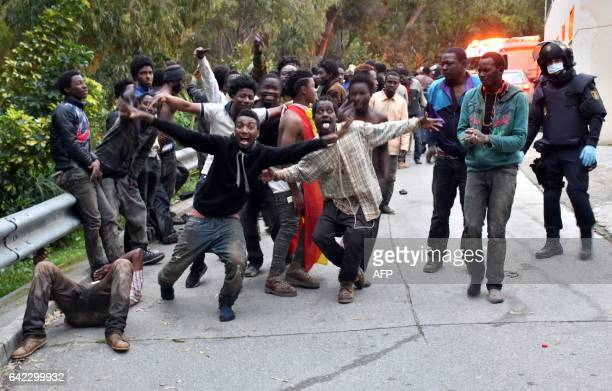 Migrants celebrate outside the Center for Temporary Stay of Immigrants after forcing their way through a fence between Morocco and the tiny Spanish...