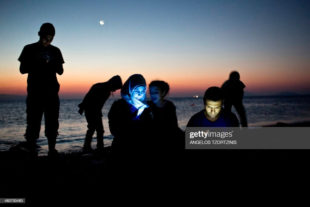 Migrants check their mobile phones after getting out of an inflatable boat on a beach on the Greek island of Kos, after crossing a part of the Aegean Sea between Turkey and Greece, on August 12, 2015. The number of migrants and refugees arriving on Greece's shores has exploded this year, but the Mediterranean country provides virtually no reception facilities and leaves them wallowing in 'totally shameful' conditions, a UN official said on August 7. The UN refugee agency's division for Europe said 124,000 refugees and migrants have landed in Greece since the beginning of the year. / AFP / ANGELOS