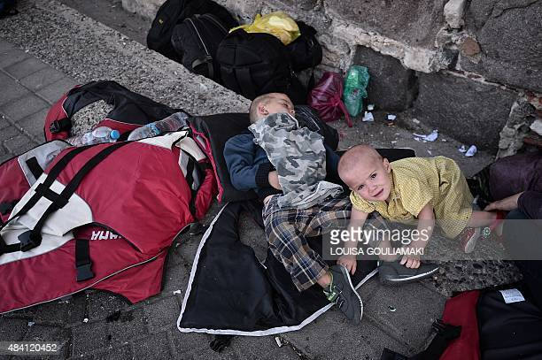 Migrants children on the sidewalk near the port of the Greek Aegean island of Kos on August 15 2015 Authorities on the island of Kos have been so...