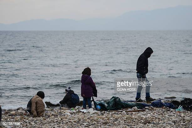 Migrants' children wait onto a pebble beach in the Yesil liman district of Canakkale northwestern Turkey after being stopped by Turkish police in...