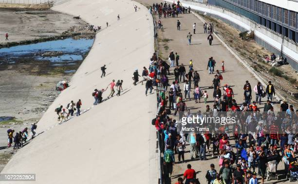 Migrants climb up a bank of the nearly dry Tijuana River as they make their way around a police blockade toward the El Chaparral port of entry on...