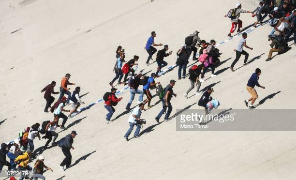 Migrants climb up a bank of the nearly dry Tijuana River as they attempt to make their way past a police blockade to the El Chaparral port of entry...