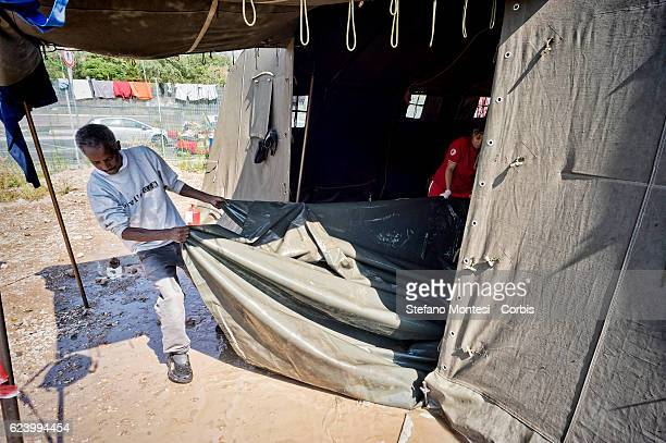 Migrants comes out of the tent flooded by rain with a tarp at a camp setup by the Red Cross close to the Tiburtina train station in Rome Hundreds of...