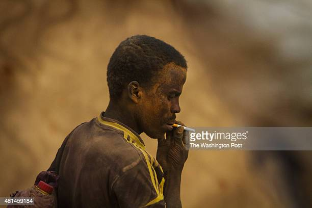 AGADEZ NIGER Migrants covered in sand and dust exit the pickup truck they were traveling in after returning from the Sahara desert They returned to...